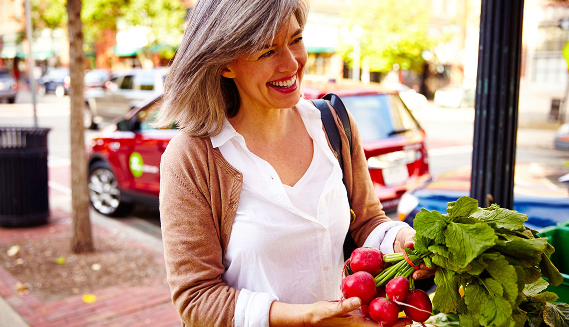 Woman looking at flowers with Zipcar behind her