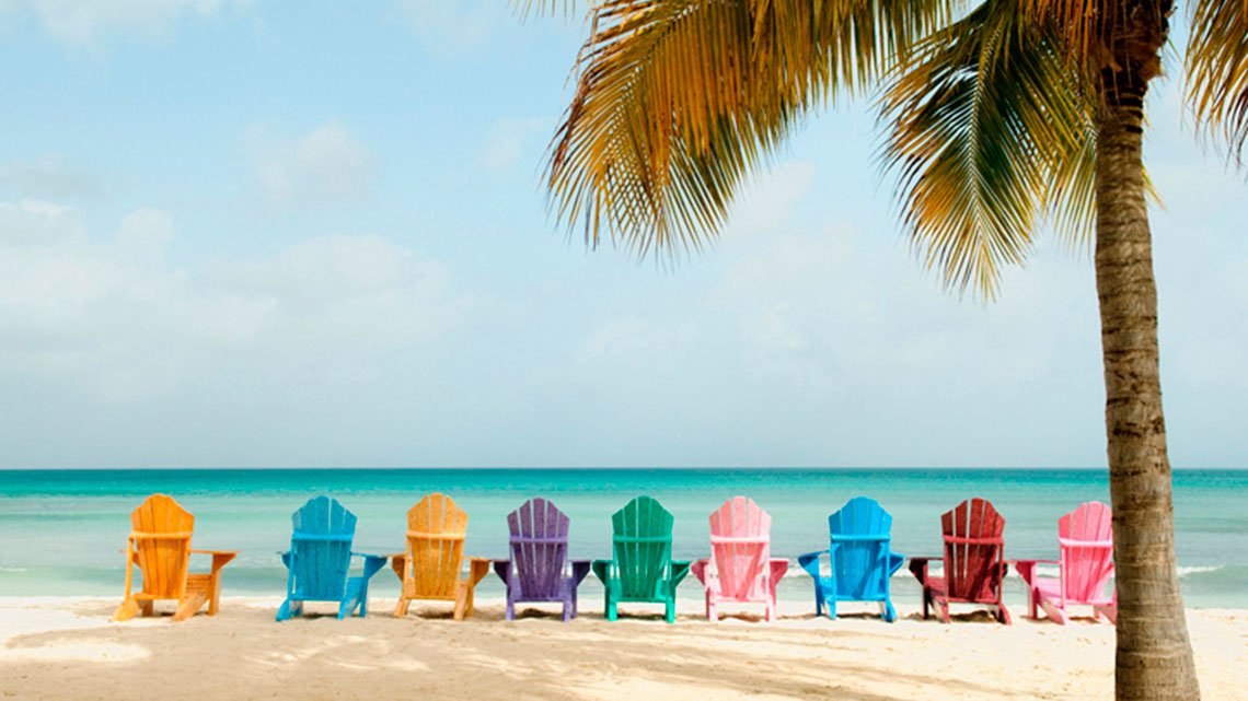 Nine colorful beach chairs sitting on the beach facing the water