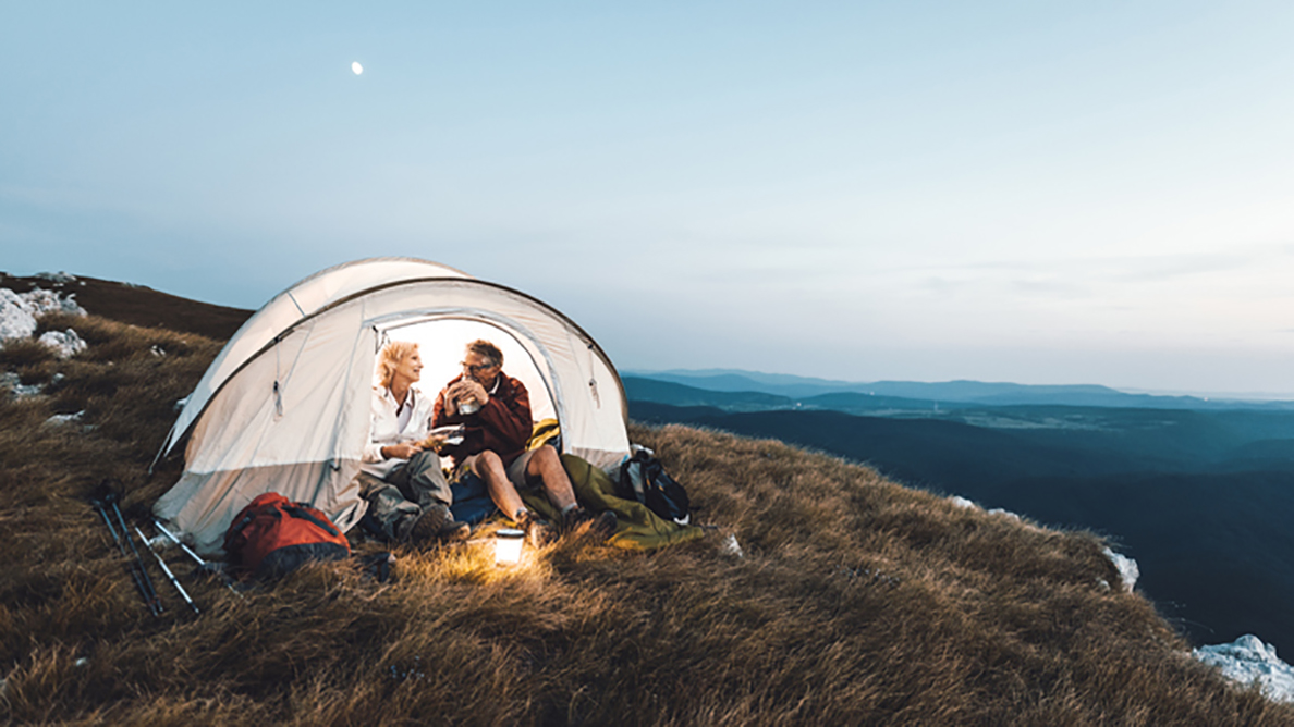 Couple tent mountainside eating
