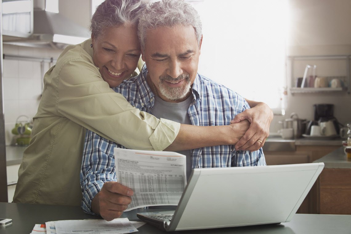 black couple smiling while looking at financial document