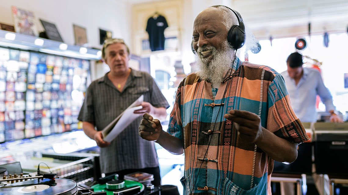 Elderly black man listening to music while wearing headphones. Black is Record shop owner and other man are in the background.