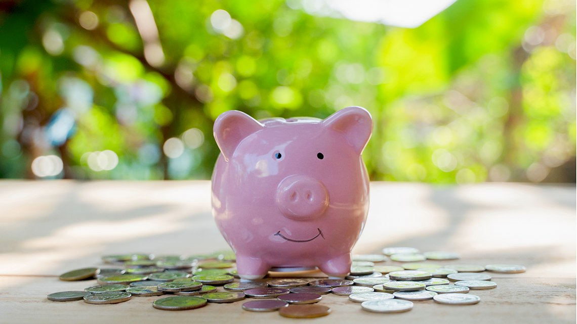 Piggy pink bank and gold coin on wood floor with green bokeh background