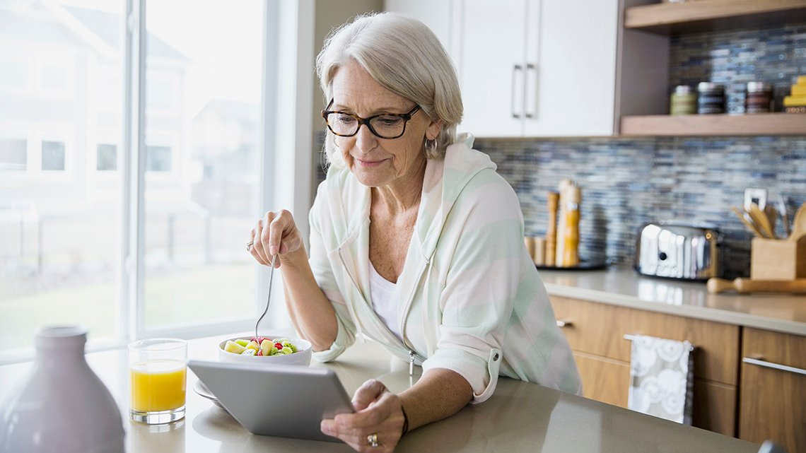 woman in kitchen eating while on tablet