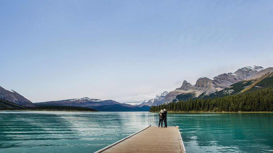 Couple standing end pier, lake, mountains