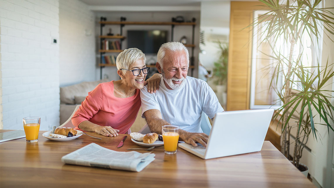 Senior couple shopping online from their home