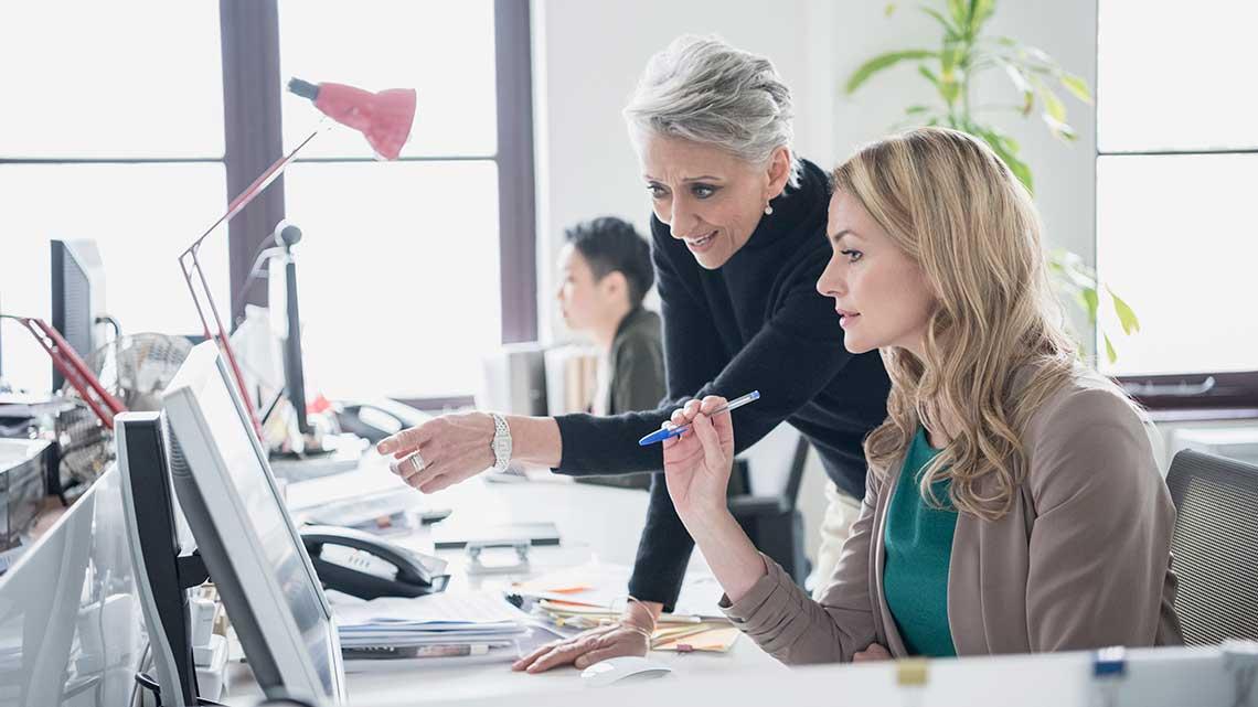 Mujer feliz sonriendo en la mesa de su oficina frente a un laptop