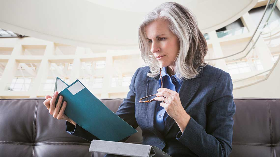Caucasian businesswoman using digital tablet while reading documents