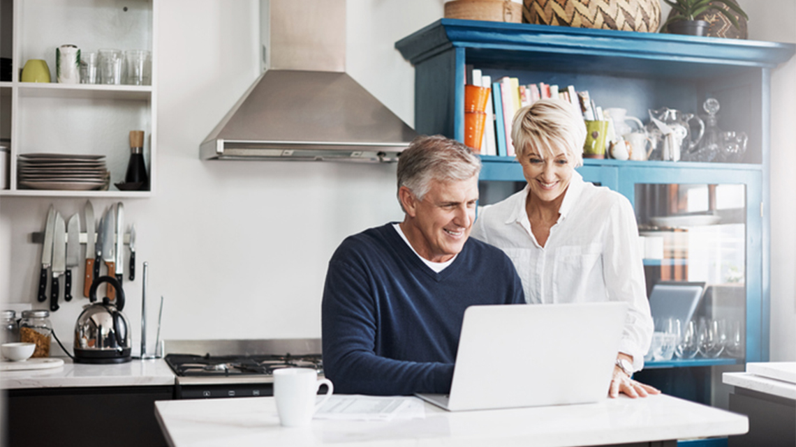 mature couple laptop kitchen