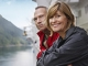 Smiling couple leaning on cruise ship railing