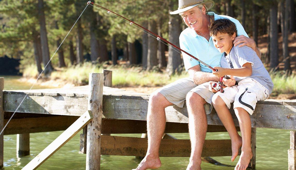 Un abuelo le explica a un nieto en un muelle cómo pescar
