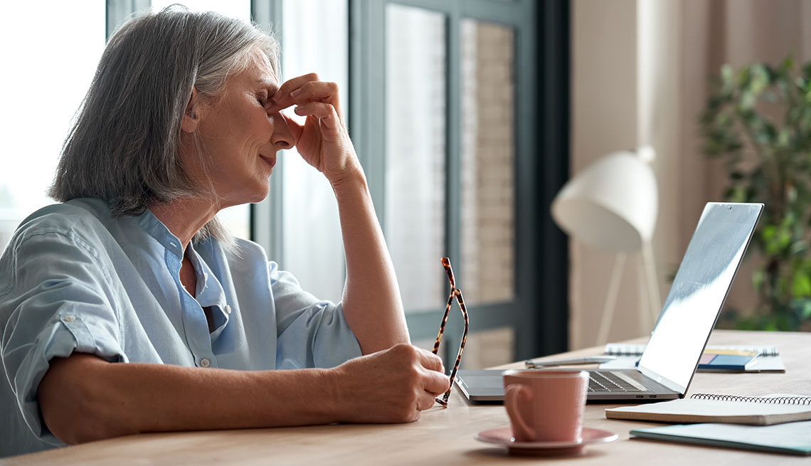 woman using a computer holding her glasses and rubbing her eyes