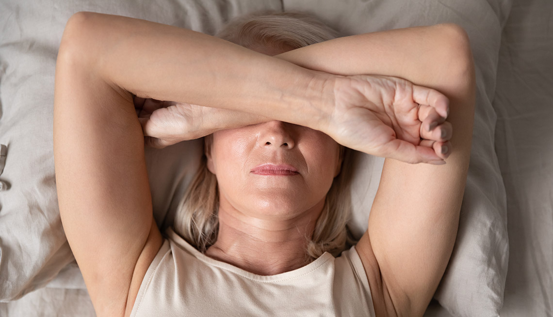 Woman sleeping with her arms crossed over her eyes