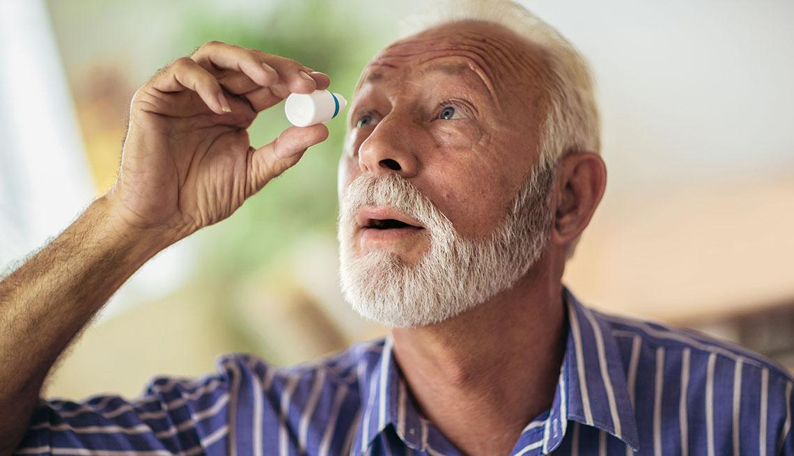 A man putting in eye drops