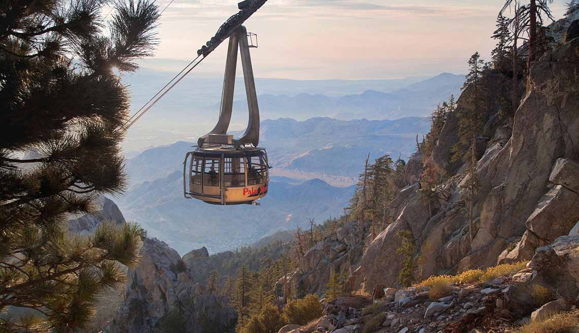 a palm springs aerial tramway car being lifted through the mountains