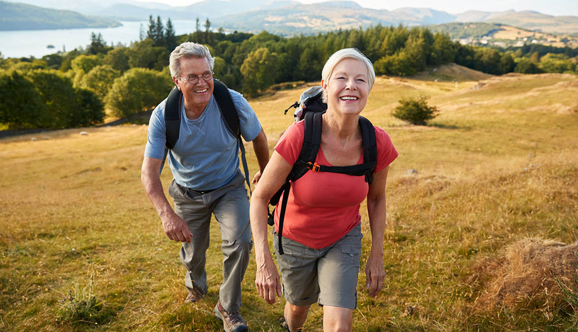 a man and woman walking on a hill wearing hiking gear