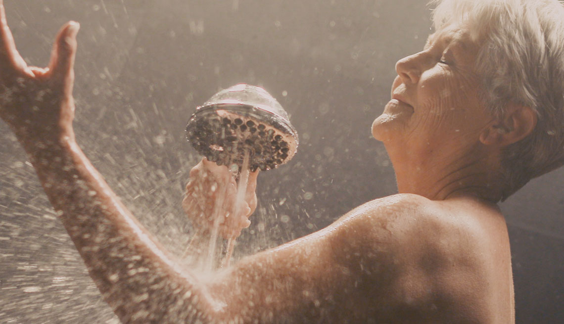 A woman in a shower using therapeutic massage shower head