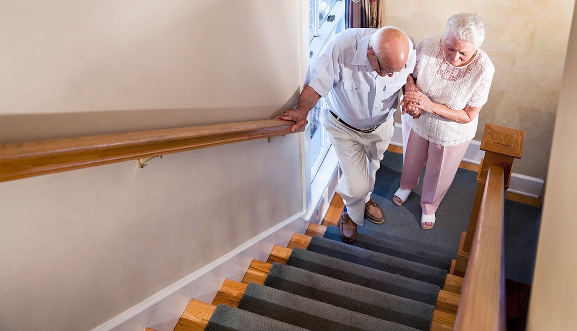 Woman helping older man up stairs