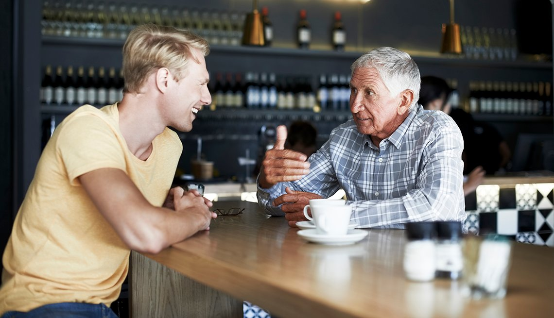 Adult son and his father having coffee together at a cafe