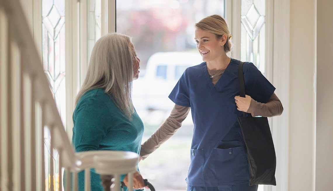 Nurse talking to patient in front door of home
