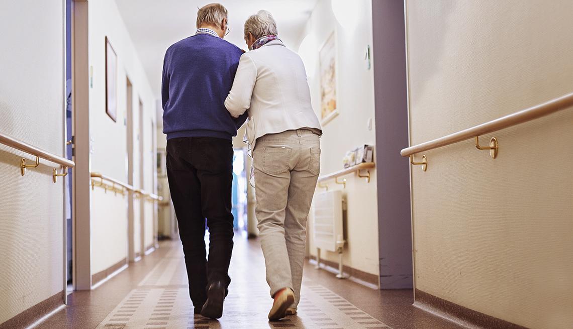 mature couple walk down a hallway