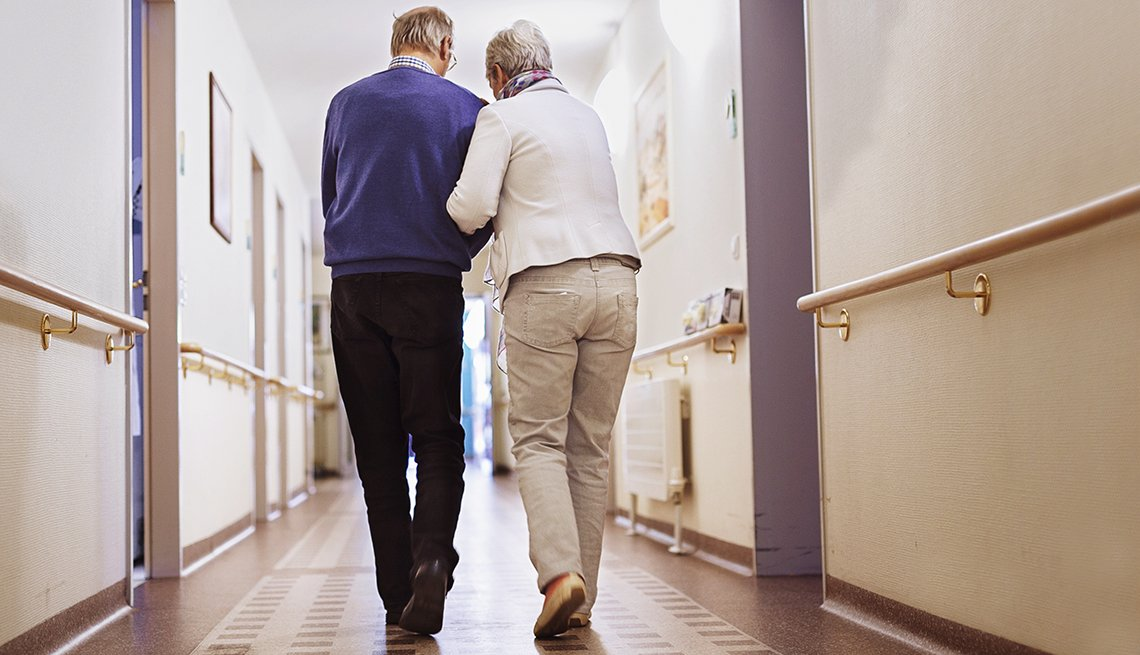 mature couple walk down a hallway