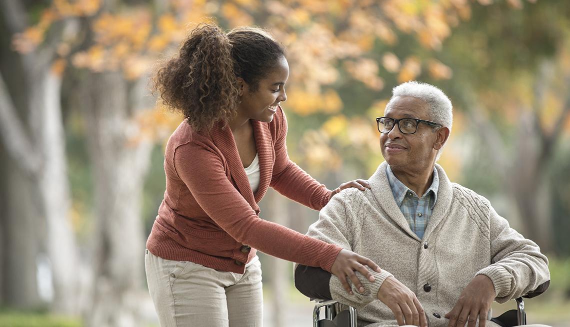 Mujer joven lleva a su padre en silla de ruedas.