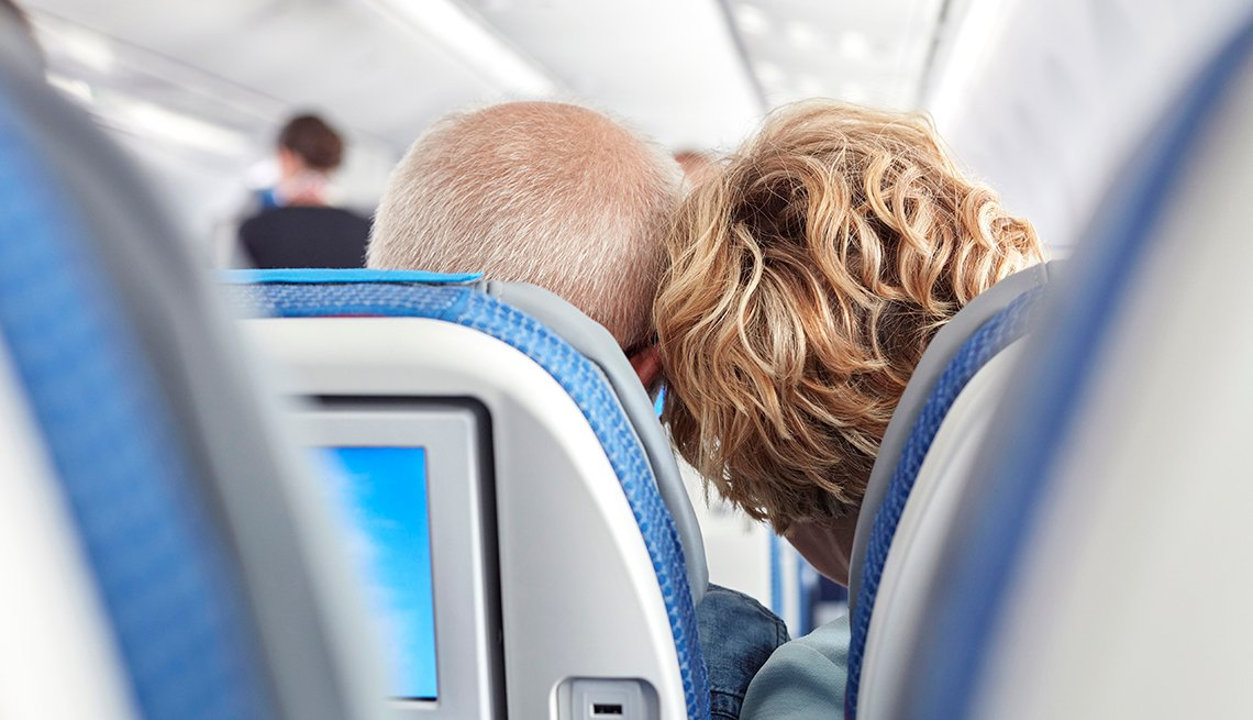 Rear view of affectionate mature couple on airplane