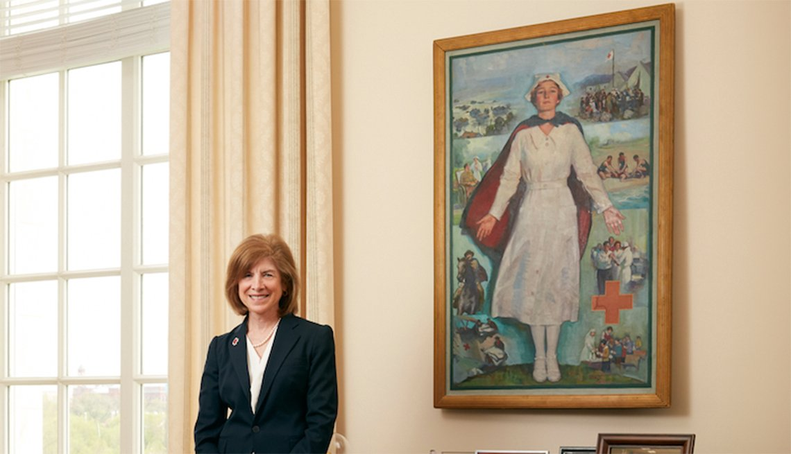 American Red Cross CEO Gail McGovern standing by a painting of a Red Cross nurse.