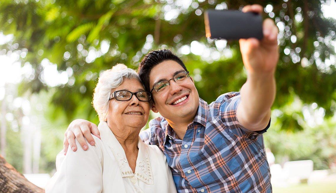 Un nieto y su abuela sonríen mientras se toman una selfie.
