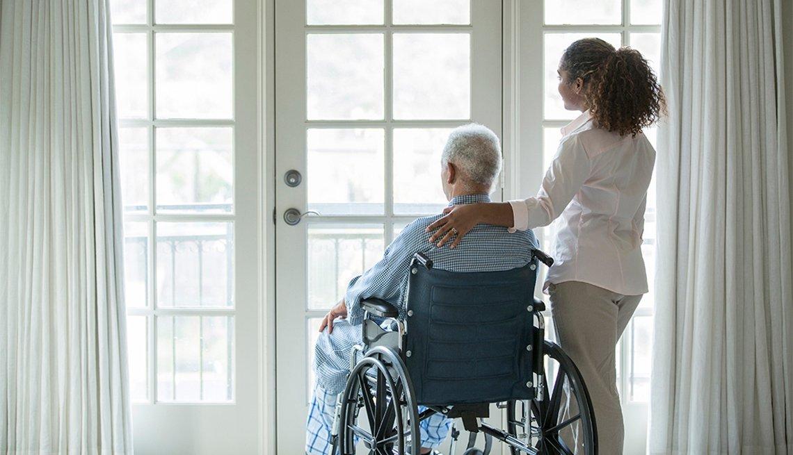 Hombre en silla de ruedas y su cuidadora