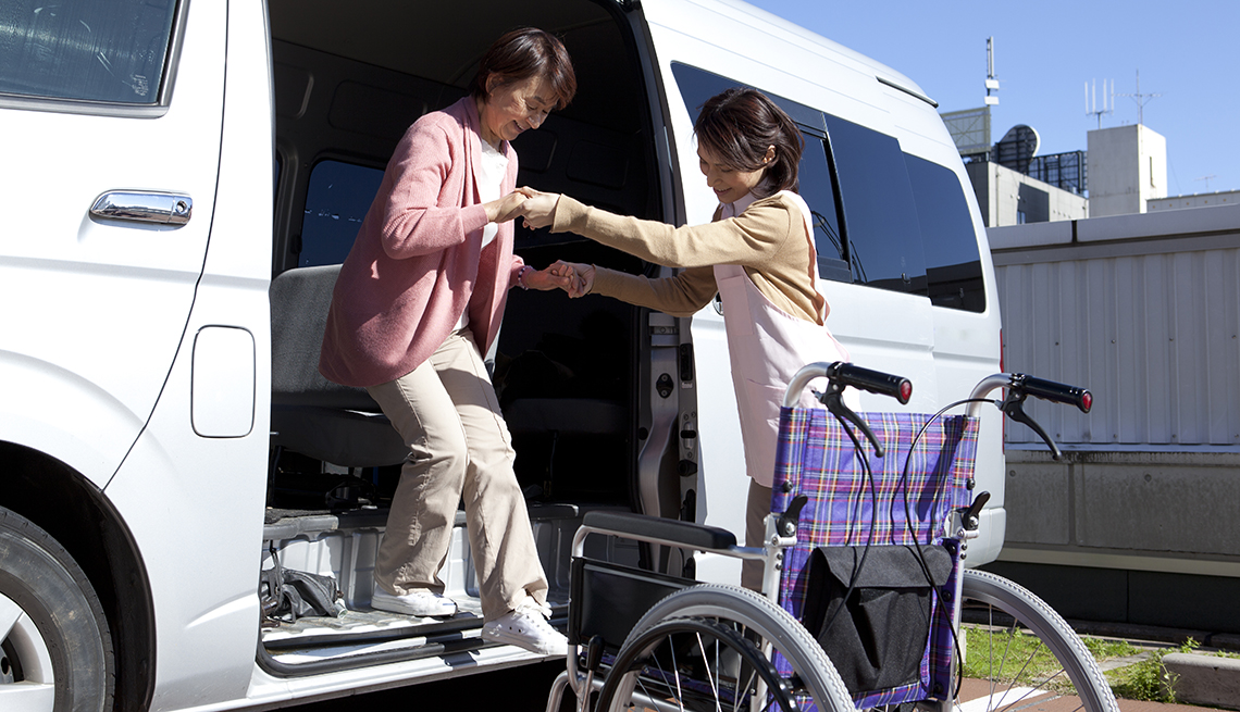 Female caregiver helping  woman step from a van into a wheelchair
