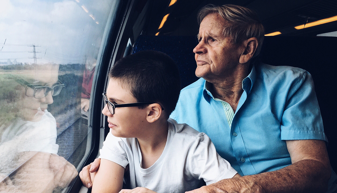 Older man and young boy traveling in a train looking out the window