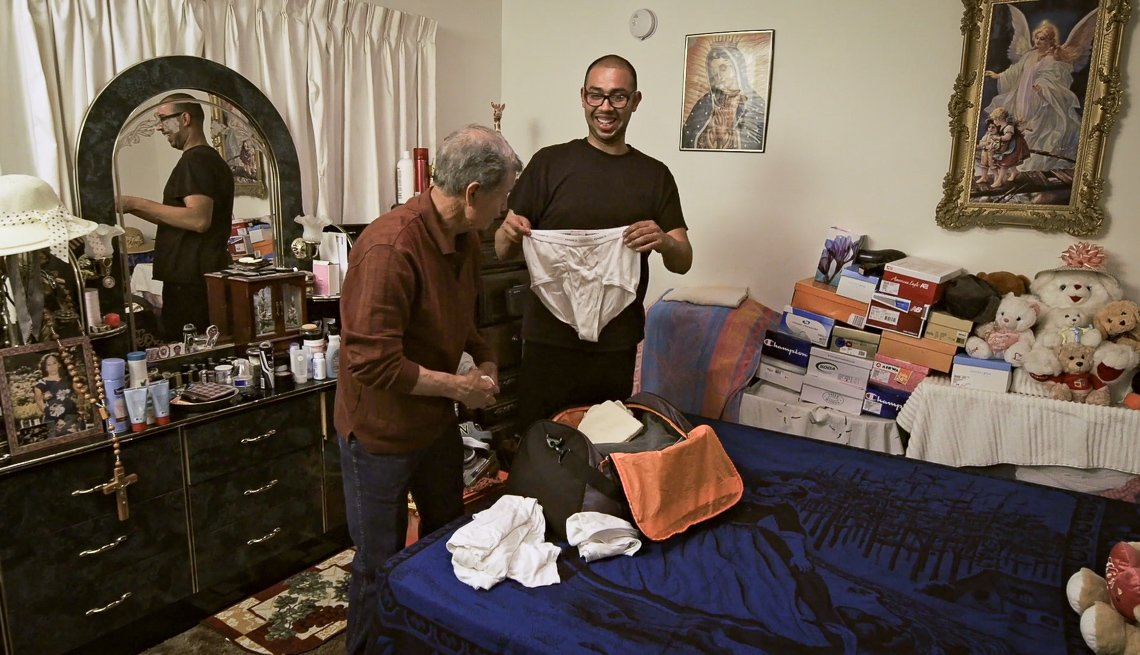 item 6 of Gallery image - Comedian Jesus Trejo holding up a pair of underwear and laughing while packing. Talking to an older man.