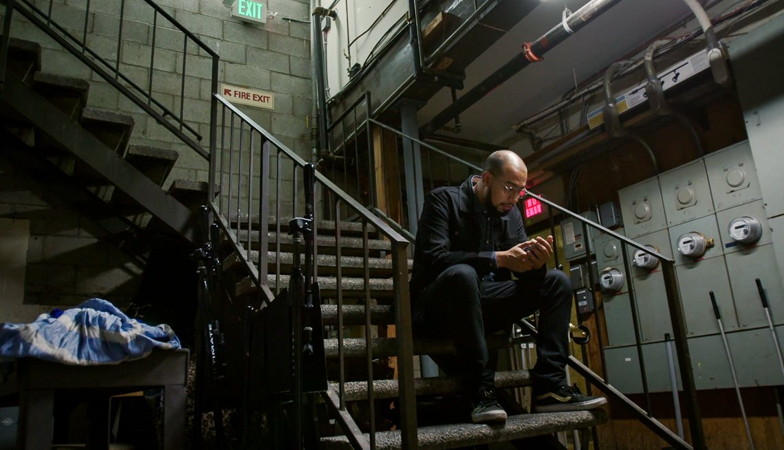 item 4 of Gallery image - Comedian Jesus Trejo sitting on steps, looking at his phone.