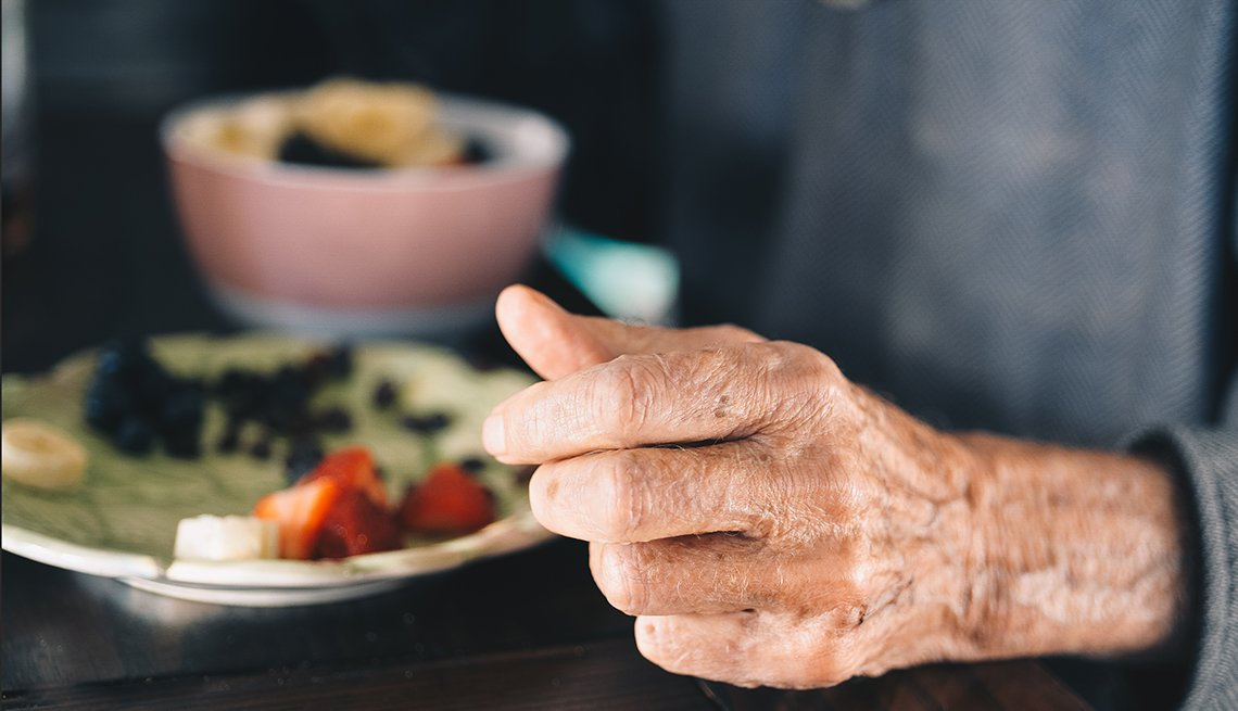 Hand of an elderly man who is sitting at a table with a bowl of fruit and cereal
