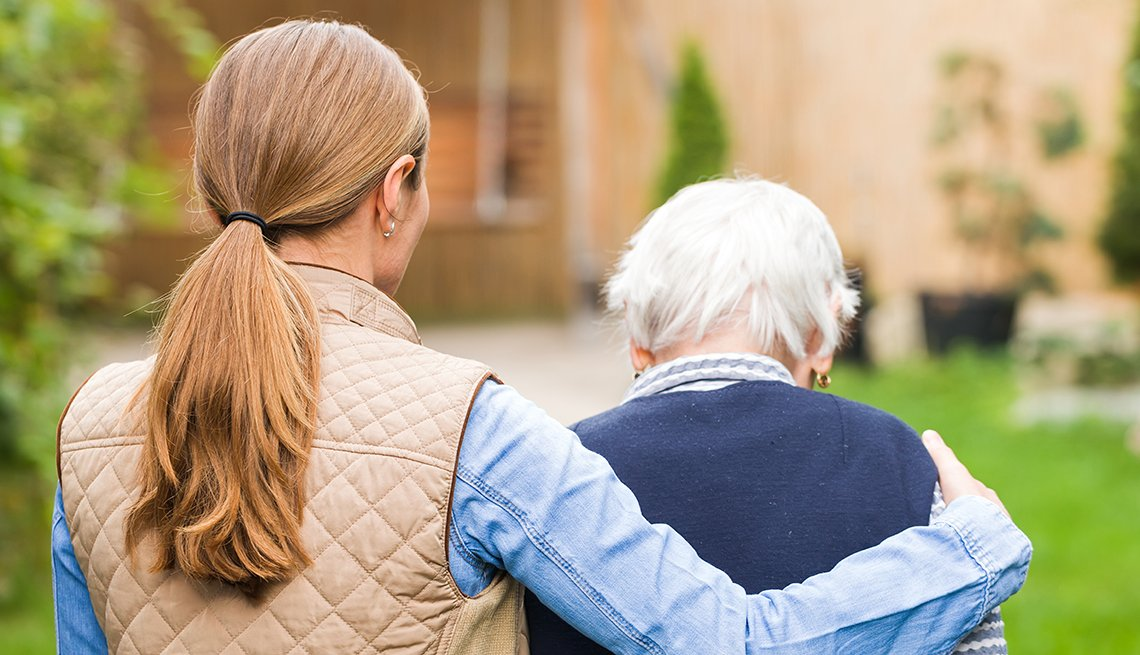 View from the back, younger female caregiver walking with her around an elderly woman. Set outdoors.