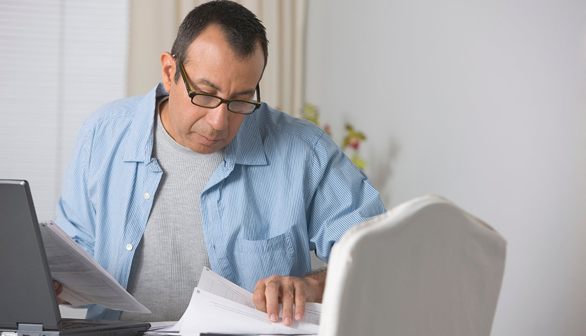 Man sitting behind a computer, looking at  insurance claim paperwork