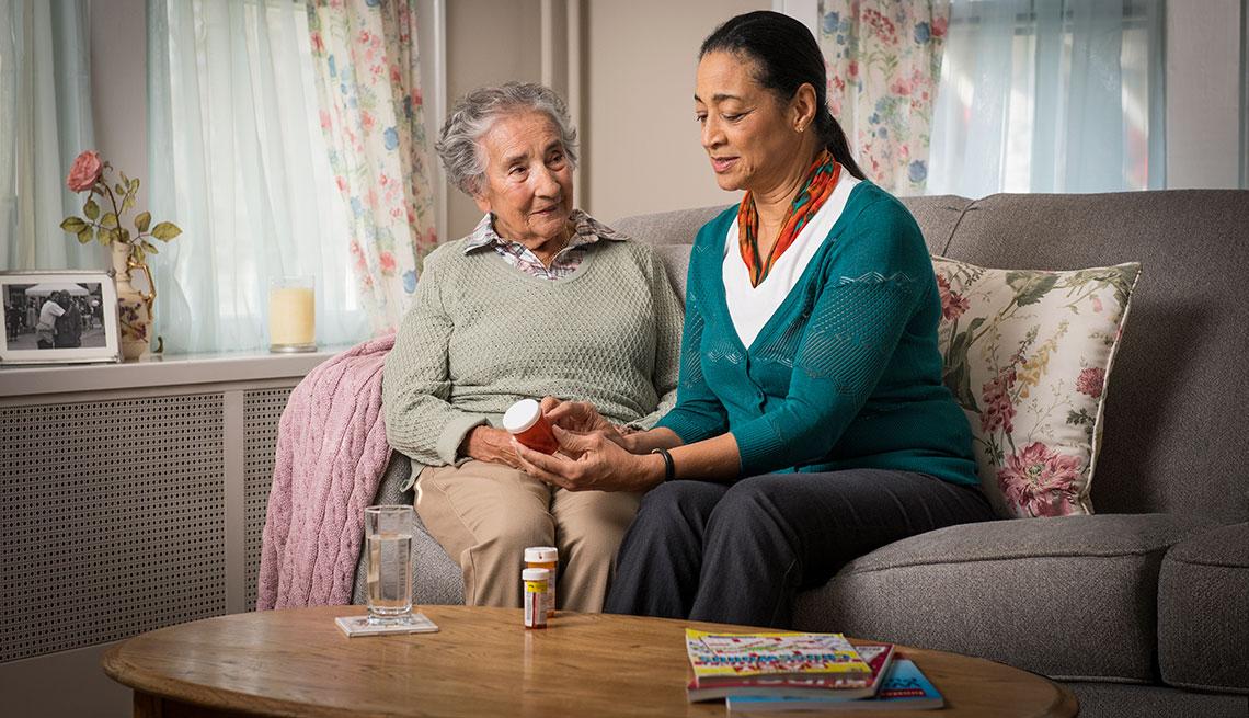 Mujer en edad adulta leyendo un medicamento a una abuelita.