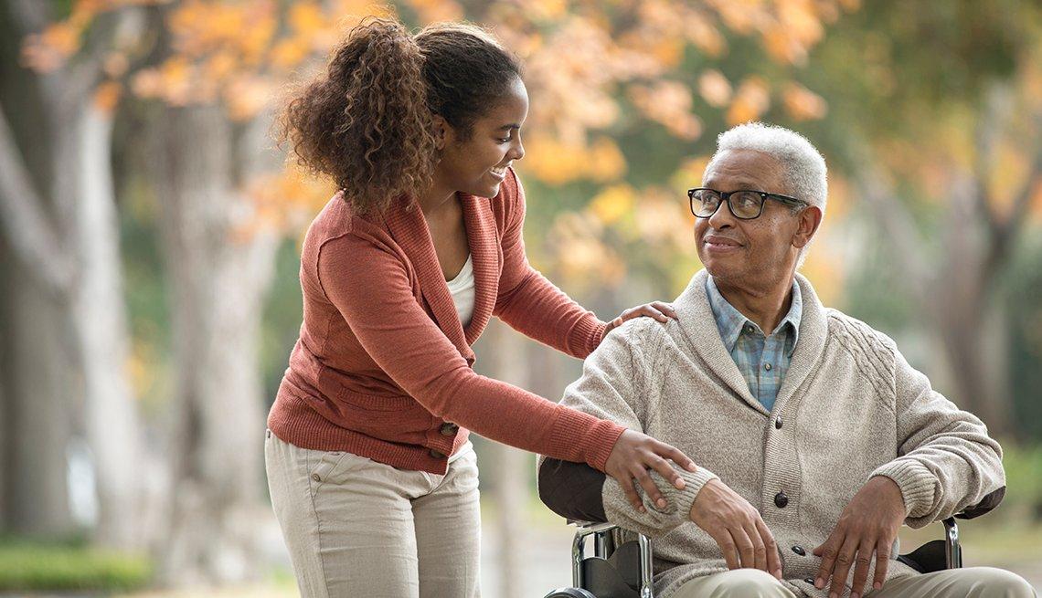 Woman caregiver pushes man in a wheelchair