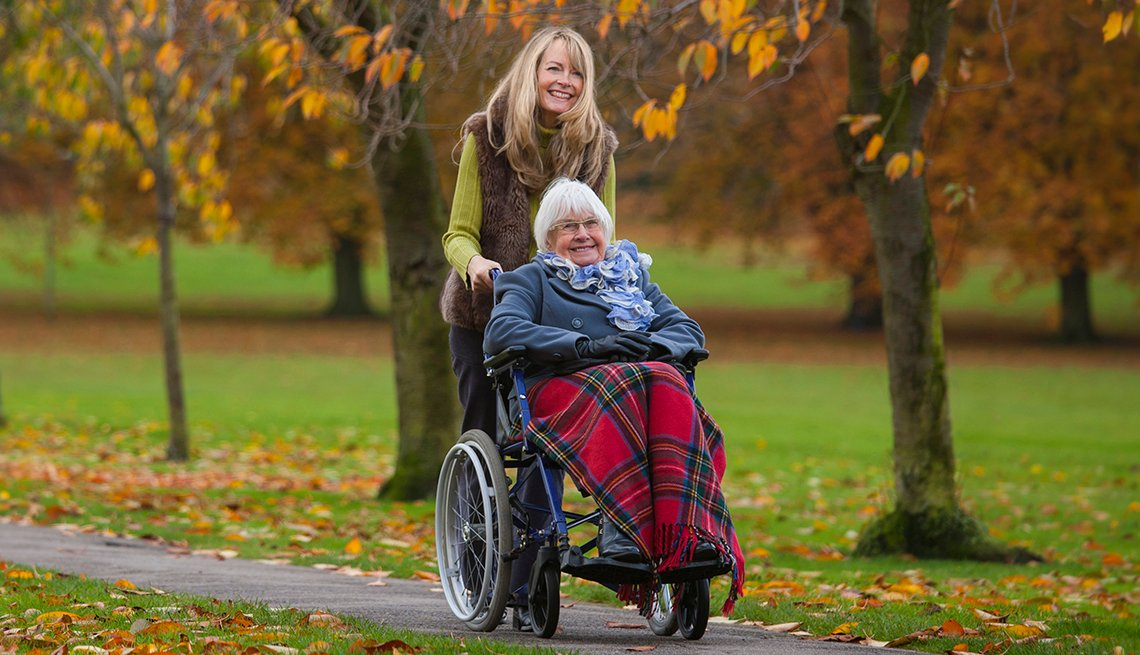 Caregiver pushing a woman in a wheelchair on a tree-lined path