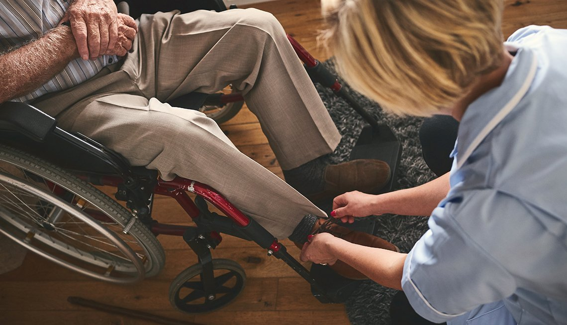 A woman helping a man in a wheelchair, tie shoe laces.