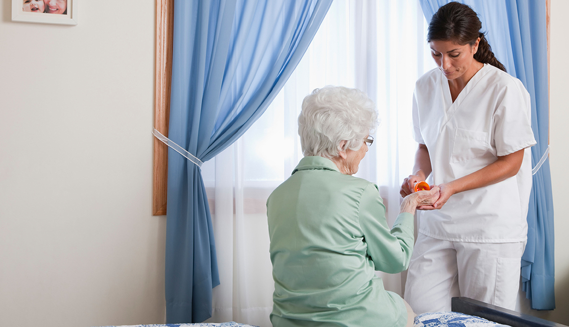 Nurse giving woman in nursing home her medication