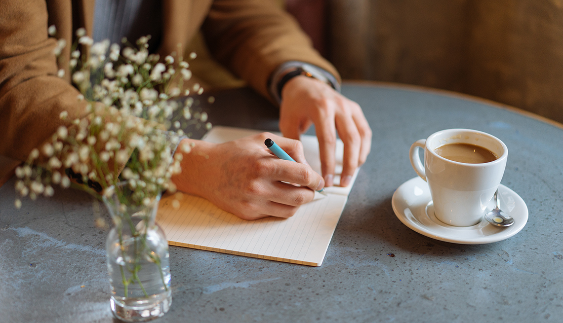 Woman at a table writing a letter. A cup of coffee and vase of flowers are on the table.
