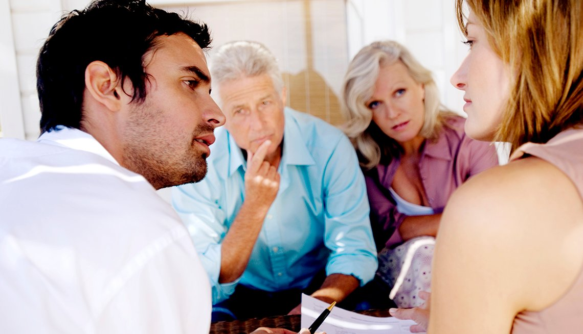 Adult brother and sister reviewing a caregiving document with their parents.