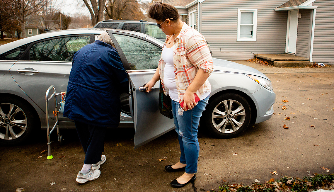 Rachel Hiles helping her grandmother into the car