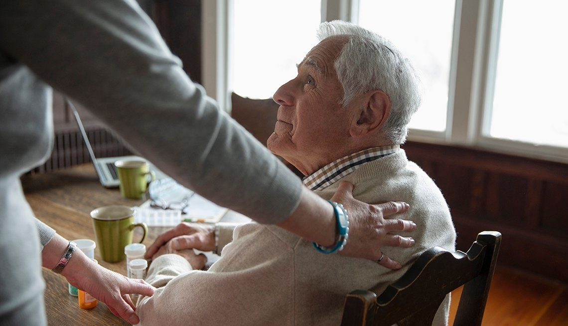 Home caregiver comforting senior man sitting at kitchen table