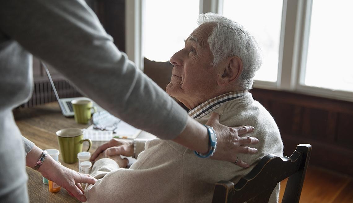 Home caregiver comforting senior man sitting at kitchen table