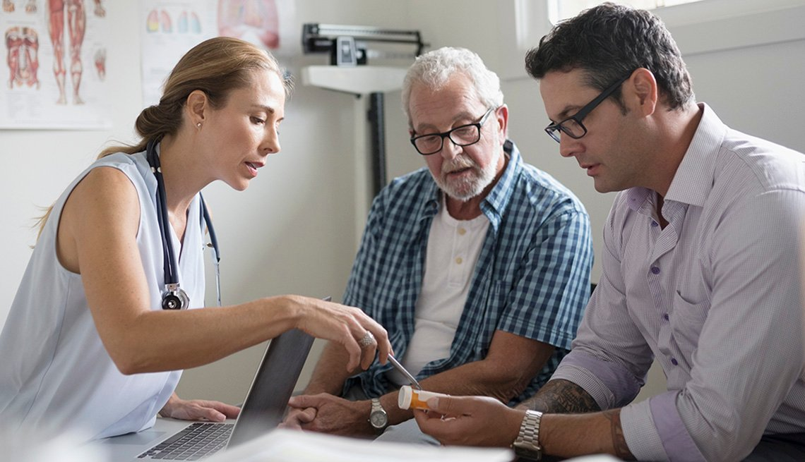 A doctor, elderly patient and caregiver reviewing prescription information