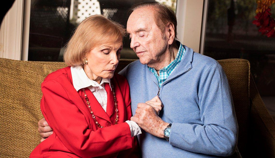 Warren Adler se sienta con su esposa en el sofá, tomados de la mano