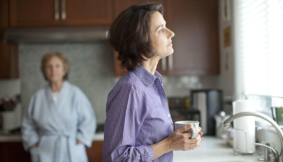 Mujer tomando café y otra mujer mayor al fondo